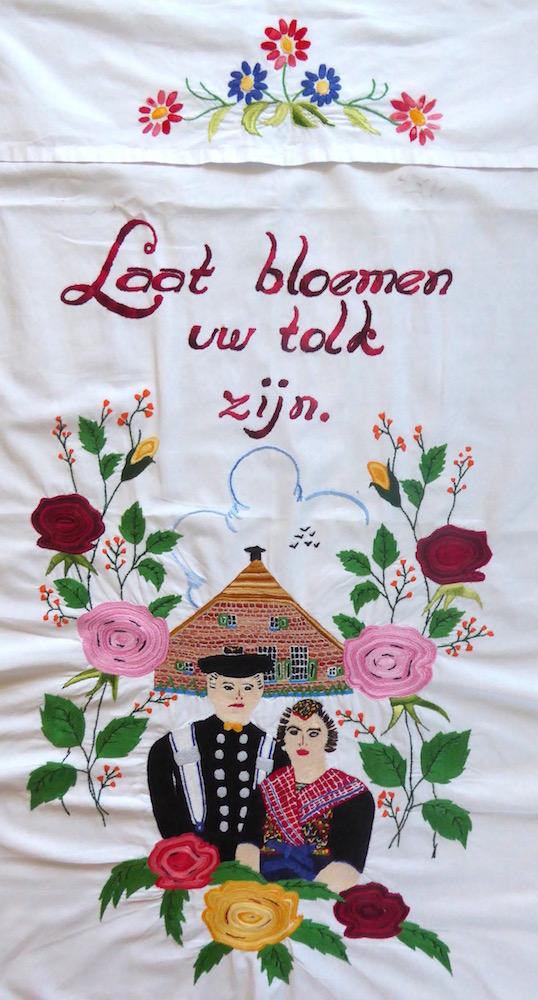 Geborduurde voordoek met Staphorster echtpaar en tekst: Laat bloemen uw tolk zijn